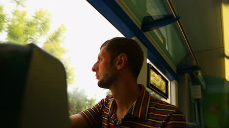 meio : Guy looking through window on train, young man traveling by railway transport Stock Footage
