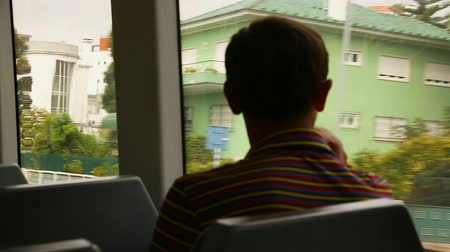 vakáció : Young man sitting and looking at view through moving train window, commuting Stock mozgókép