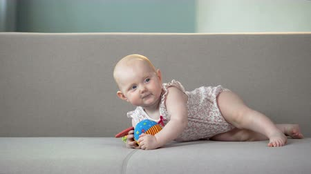 ползком : Cheerful baby girl playing with colorful toys on sofa, infant learning to crawl Стоковые видеозаписи