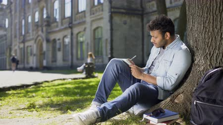 charged : Multiracial male sitting on grass under tree, writing in notebook, creative idea