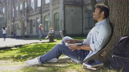 admission : Mixed-race young guy using laptop under tree, getting bad news, disappointment Stock Footage