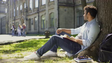 ler : Young male sitting under tree with book looking around, having pleasant thoughts