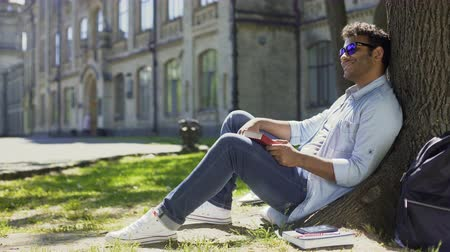 charged : Multiracial man sitting under tree wearing sunglasses, positive mood, energy
