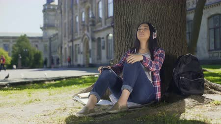 charged : Asian female in headphones enjoying music, sitting under tree, favorite band Stock Footage
