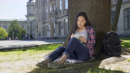 dizgi : Multinational young woman taking notes in notebook sitting under tree, essay