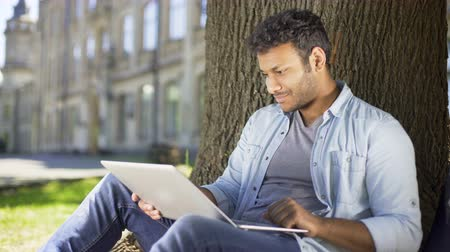 оценка : Multiracial college student sitting under tree with laptop, checking final paper Стоковые видеозаписи