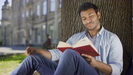 enjoyable : Young man sitting under tree reading book and thinking, literature, fiction