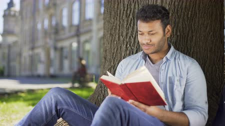 favori : Male reading favorite novel under tree, pressing book against chest, daydreaming Stok Video