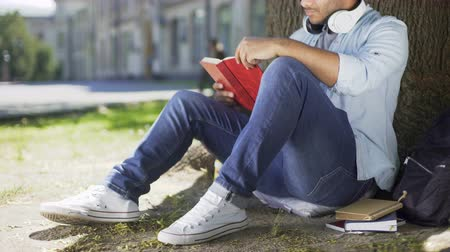 literary : College student sitting under tree, taking book to read, literary studies, class
