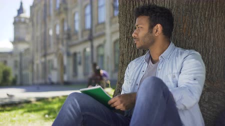 dizgi : Multinational guy sitting under tree, writing in notebook, thinking, composer