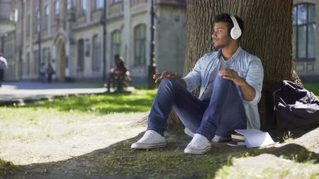 positive vibes : Young man putting headphones, listening to music sitting under tree, admiration