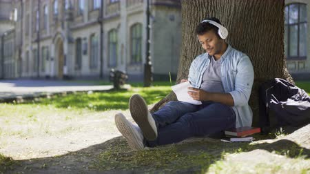 multinational : Mixed-race guy sitting under tree in headphones writing in notebook, song writer Stock Footage