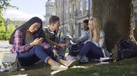 připomínka : Classmates sitting under tree, girl touching guys arm, friendship and flirt