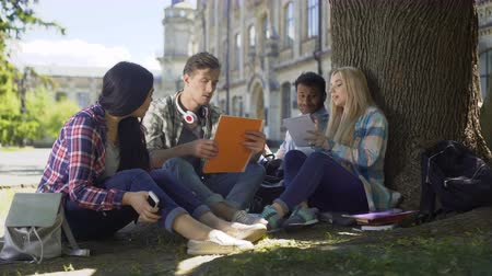 cooperar : University students gathered under tree, having discussion, working on project Vídeos
