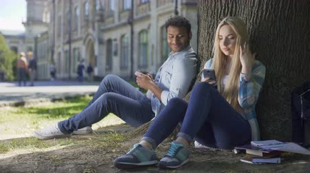 döküm : Young man, woman sitting under tree with cellphones, casting looks at each other Stok Video