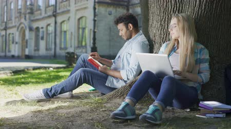 indecisiveness : Guy reading book under tree, girl using laptop, casting looks at each other