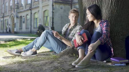 interessado : Male and female strangers sitting under tree, having conversation, acquaintance