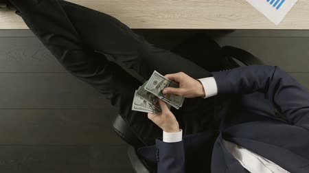 зарабатывать : Satisfied businessman sitting at office table and counting dollars, success Стоковые видеозаписи