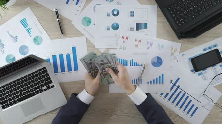 task : Boss counting dollar banknotes at workplace, bribery, profitable business Stock Footage