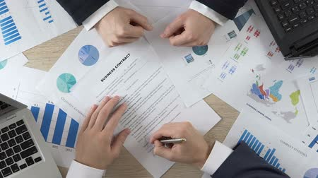 assinatura : Top of view of businessperson signing business contract, men shaking hands