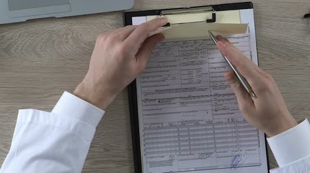 physician : Male doctor checking his medicine prescription and signing health insurance form
