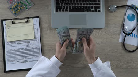 corruptible : General practitioner counting cash earned on treatment of private patient, money Stock Footage