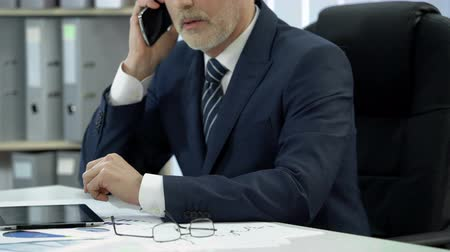 ünnepélyes : Businessman in suit working in office, dialing and talking to client over phone Stock mozgókép
