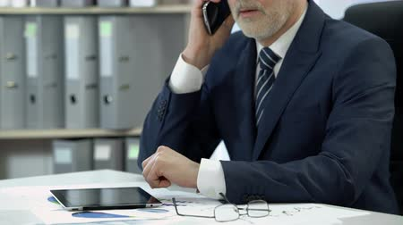 tárcsázás : Man in business suit dialing, talking on cell phone, tablet and glasses on table