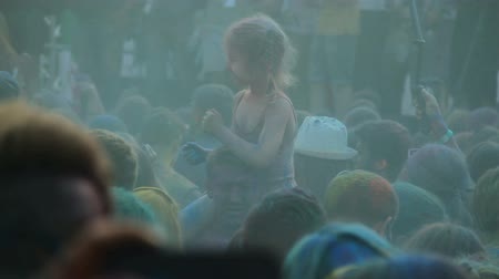 eufória : Crowd of people covered in colored paint hanging out at Holi color festival