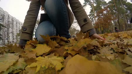 проливая : Lonely woman walking through autumn park, throwing up fallen golden leaves Стоковые видеозаписи