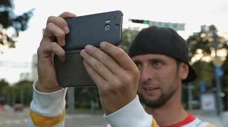 takes : Funny man in cap filming video on smartphone in the street, modern clothing Stock Footage
