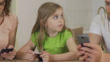 indifference : Little girl suffering from lack of parental warmth, mom and dad using phone