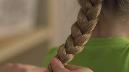 braids : Mother braiding blonde daughters hair, hairstyle, family relations and care Stock Footage
