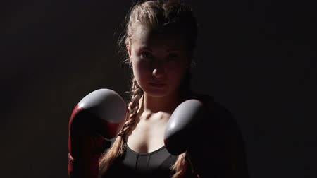 self defense : Serious Muay Thai woman boxer looking into camera, motivation and goals, sport