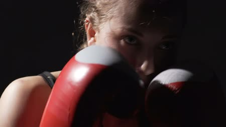 self motivated : Hard-working female boxer wearing boxing gloves, air punching in gym, training