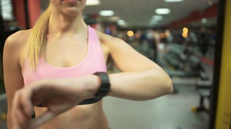 мониторинг : Female setting up smart watch before starting training in gym, fitness app Стоковые видеозаписи