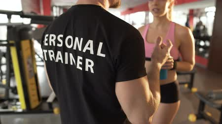 danışma : Conversation between personal trainer and his female trainee in gym on a break Stok Video