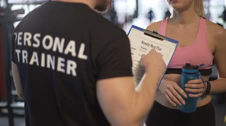 semanal : Personal trainer discussing weekly meal plan with female client in the gym Stock Footage