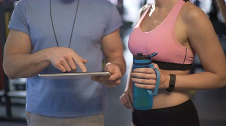 sports nutrition : Coach explaining training schedule to female client, using tablet in the gym