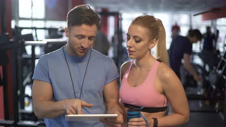nicely : Trainer and his attractive female client discussing workout program in gym