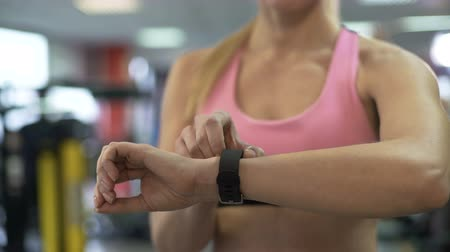 fitness tracker : Fit woman clearing indicators of health bracelet before starting workout in gym Stock Footage