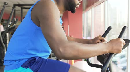 stationary : Motivated man riding a stationary bike, shaping up his body in the gym Stock Footage
