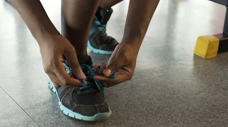 cadarço : Athletic Afro-American male tying shoelaces in the fitness club, sportswear Vídeos