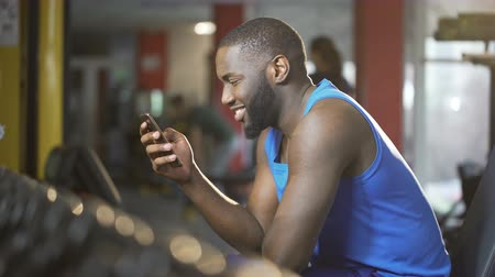 gymnasium : Young man typing message on smartphone with smile on face, break during workout Stock Footage