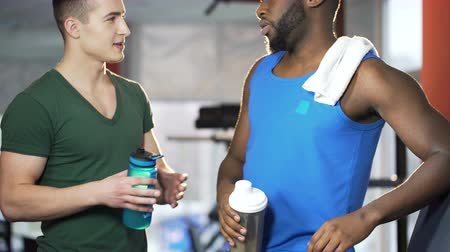 sports nutrition : Male friends talking and drinking water in gym, discussing plans after workout