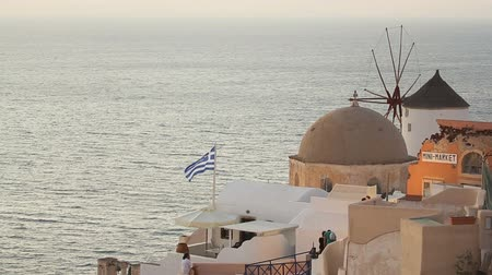 Киклады : Greek national flag waving in wind on roof of house in Santorini washed by sea Стоковые видеозаписи