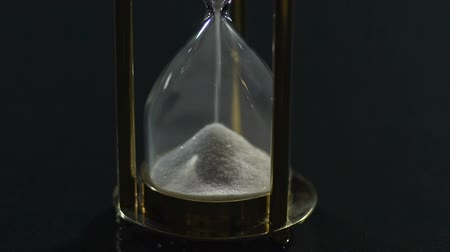 geçen : White sand flowing in hourglass, past and future, transience of life, close-up