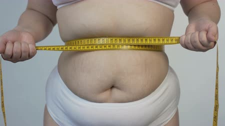 measure tape : Body hatred, corpulent woman measuring her belly and tightening tape-line, diet