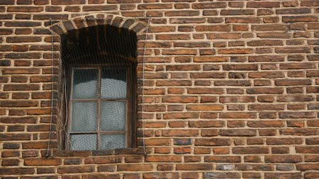 imprisonment : Window covered with metal mesh, ancient brick wall of medieval prison, captivity Stock Footage