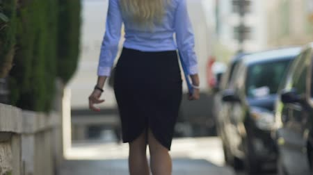 representante : Sexy blonde lady with beautiful gait slowly walking along street to her work